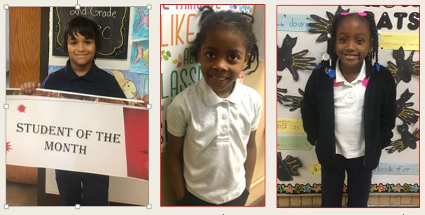 3 second graders holding signs